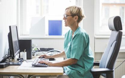 Koncentrerad kvinnlig läkare som sitter vid skrivbord på sjukhus
